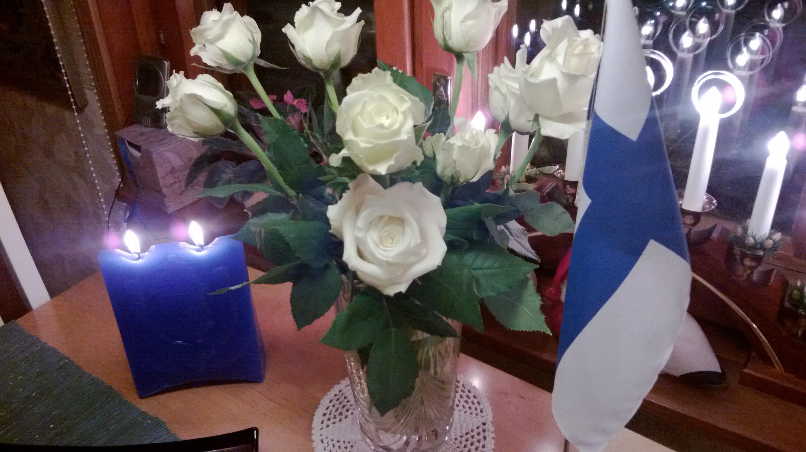 Valkoiset ruusut lippu ja kynttilä